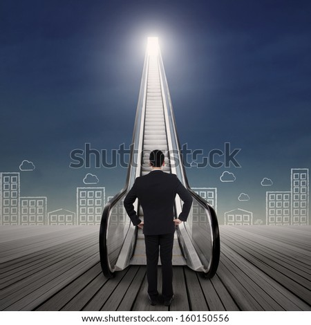 Young businessman standing at the escalator with cityscape drawing - stock photo