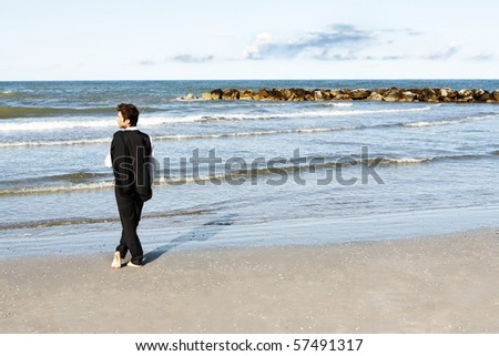 Young businessman standing barefoot on beach in suit - stock photo