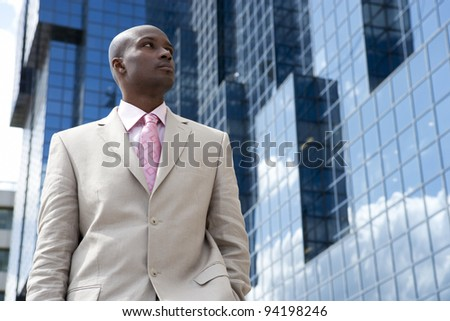 Young businessman standing by reflective office building, outdoors. - stock photo