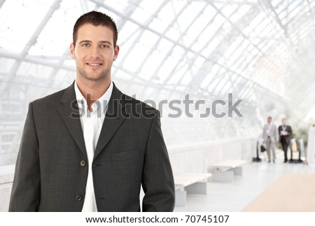 Young businessman standing in bright office lobby smiling at camera.