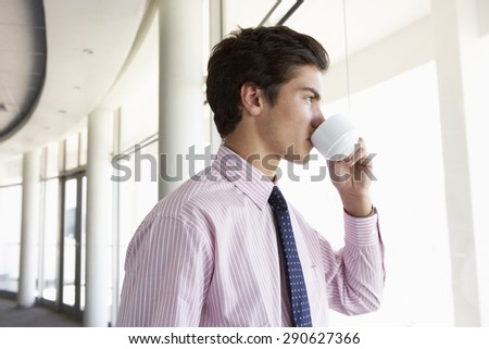 Young Businessman Standing In Corridor Of Modern Office Building Drinking Coffee - stock photo