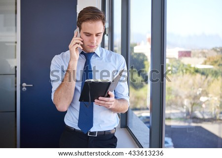 Young businessman standing in his office, talking on his mobile phone while looking at his appointment diary - stock photo