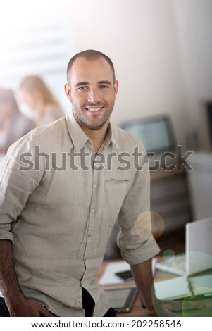 Young businessman standing in office - stock photo