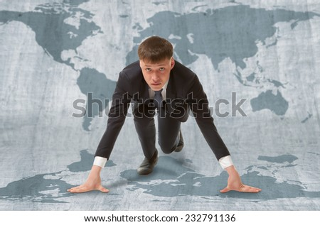 Young businessman standing in start pose ready to run.  WTO concept - stock photo