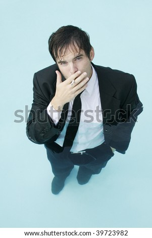 Young Businessman standing in water, smoking a cigarette.