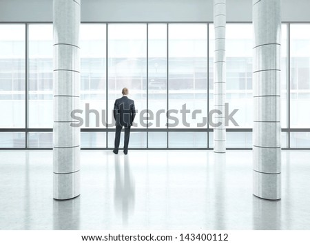 Young businessman standing into modern office - stock photo