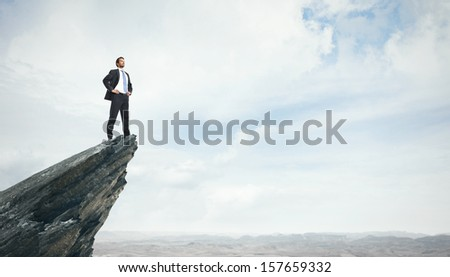 Young businessman standing on a peak - stock photo