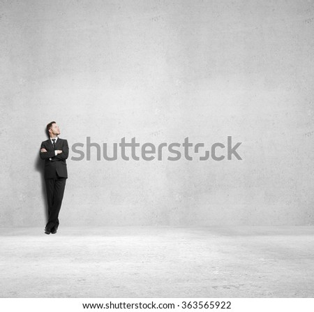 young businessman standing on concrete room - stock photo