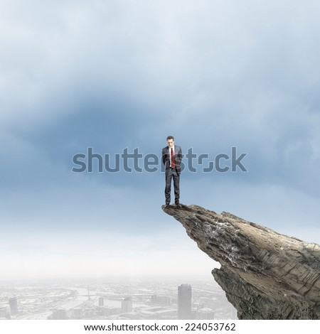 Young businessman standing on edge of rock mountain - stock photo