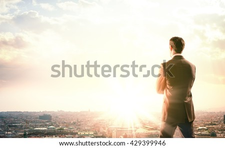 Young businessman standing on edge of rock mountain and looking at city - stock photo