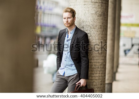 Young businessman standing on the street
