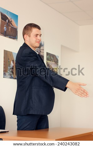 Young businessman standing over his desk offering his hand to finalise a business deal or agreement or begin a new partnership - stock photo