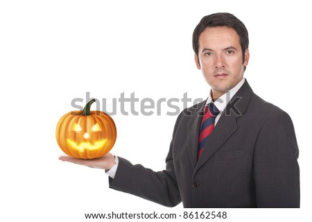 young businessman standing with a halloween pumpkin on his hand - stock photo