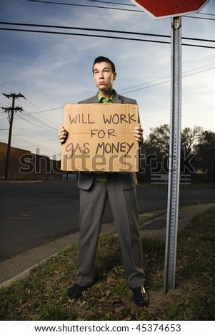 Young businessman stands on a street corner holding a sign that reads 'will work for gas money'. Vertical shot. - stock photo
