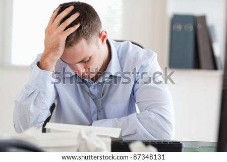 Young businessman stressed while doing his accounting - stock photo