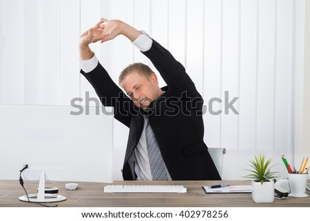 Young Businessman Stretching In Office With Computer On Desk