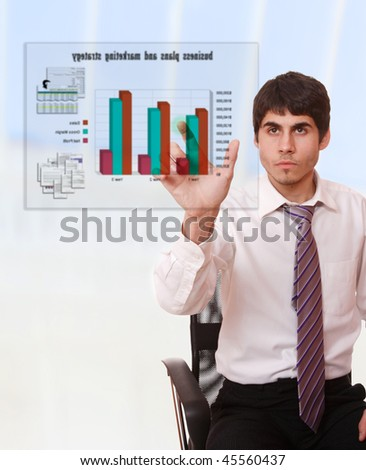 Young businessman studying a business plan on a virtual screen - stock photo