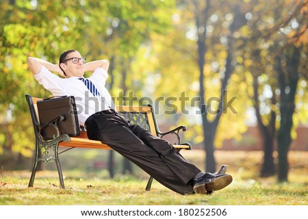 Young businessman taking a break after work seated on a bench in park - stock photo