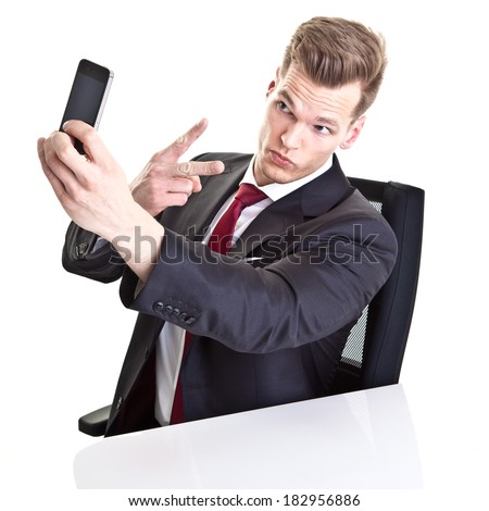 Young businessman taking a selfie with his smartphone - stock photo
