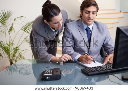 Young businessman taking notes while getting mentored by colleague