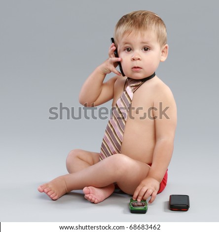 Young businessman talk on cell phone in a tie, on a grey background