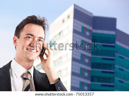 Young businessman talking at the cell phone outdoor - stock photo