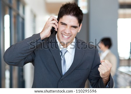 young businessman talking on cell phone and receive exciting news - stock photo