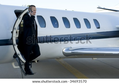 Young businessman talking on his cell phone as he leaves his corporate jet