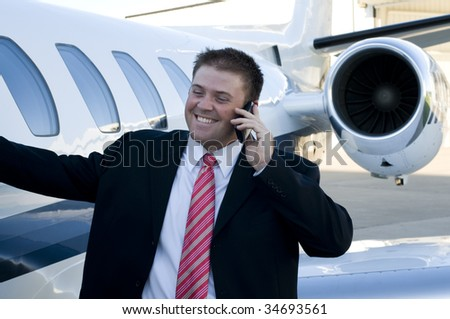Young businessman talking on his cell phone in front of his corporate jet - stock photo