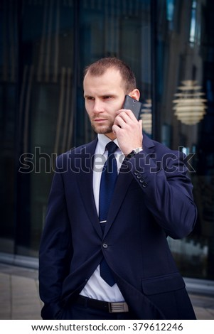 Young businessman talking on his cellphone against office building - stock photo