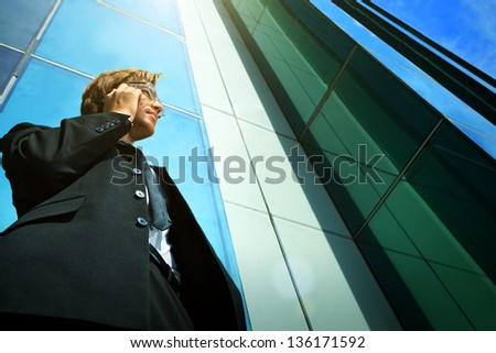 Young businessman talking on his mobile phone in the big city. - stock photo