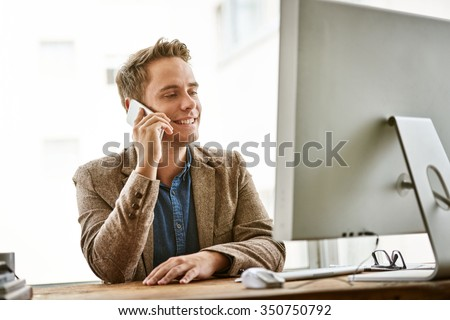 Young businessman talking on his phone while sitting at his desk at work and wearing a fashionable jacket