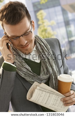 Young businessman talking on mobile phone on the way to work, holding newspaper and coffee. - stock photo