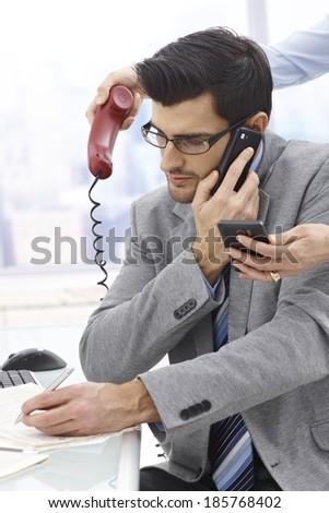 Young businessman talking on mobile writing notes, while other two phones handed towards him. - stock photo
