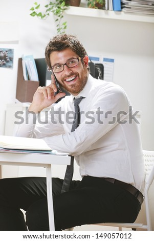 Young businessman talking on smartphone in office. Businessman with rimmed glasses working. - stock photo