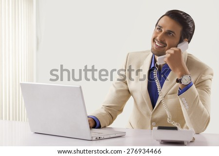Young businessman talking on telephone while using laptop at office desk