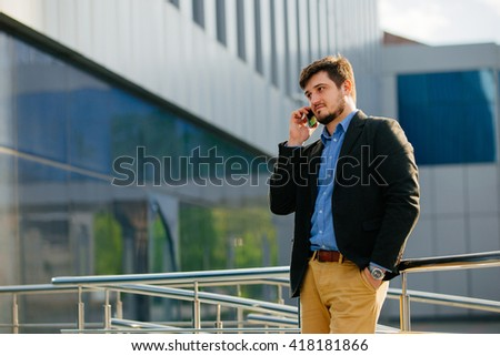 Young businessman talking on the phone near the shopping center.