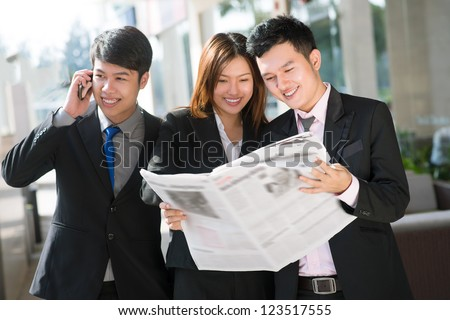 Young businessman talking on the phone while his associates reading newspaper