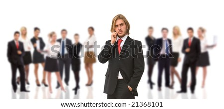 young businessman talking on the phone with his team in the back - stock photo