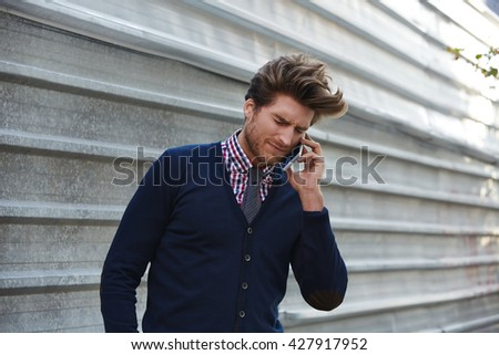 Young businessman talking smartphone phone on the street metal fence - stock photo