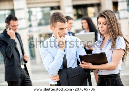 Young businessman talking to his pretty woman business partner in front of office building.