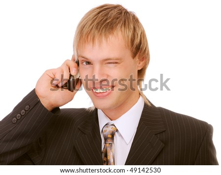 Young businessman talks by mobile phone and winks, isolated on white background.