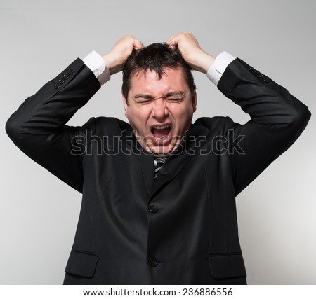 Young businessman tearing his hair - stock photo