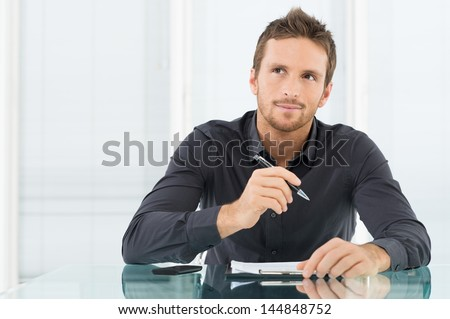 Young Businessman Thinking and Wondering While Writing a Paper - stock photo