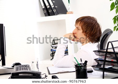 Young businessman thinking in his office