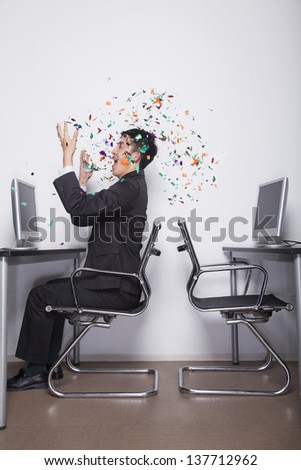 Young Businessman throwing confetti in the office - stock photo