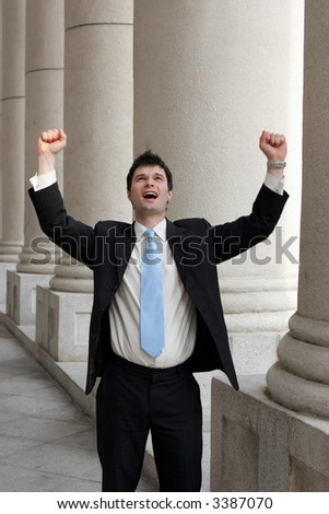 Young businessman throws his arms up in a gesture of success.