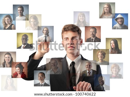 Young businessman touching icons of different people on a screen - stock photo