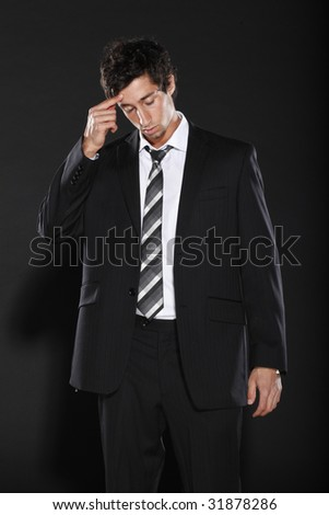 Young Businessman Touching Temple - stock photo