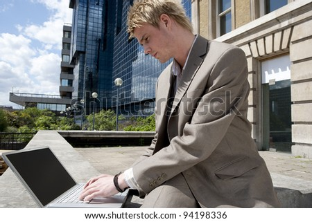 Young businessman typing on a laptop computer while sitting by modern office building, outdoors. - stock photo